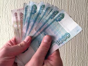 Банкноты 1000 и 100 рублей в руках изображение